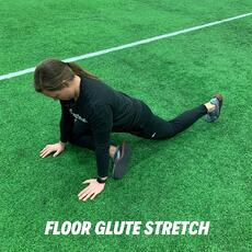 Orthopedic institute athletic trainer demonstrates the floor glute stretch to relieve low back pain.