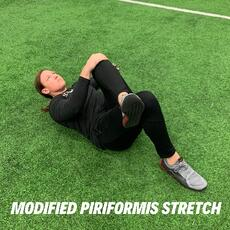 Orthopedic institute athletic trainer performs the modified piriformis stretch to relieve low back pain.