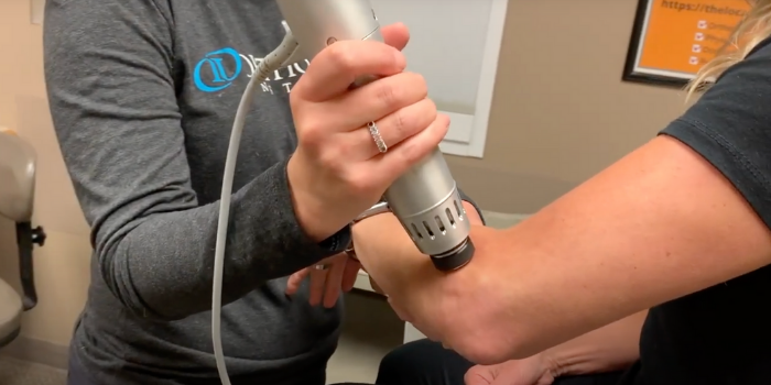 A female physical therapist applies shockwave therapy to arm of female patient near the elbow, using a handheld Radial Pulse Therapy tool to alleviate pain due to plantar fasciitis.