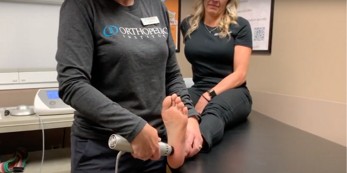 A female physical therapist manipulates the bottom of a female patients foot, near the heel, using a handheld Radial Pulse Therapy tool to alleviate pain due to plantar fasciitis.
