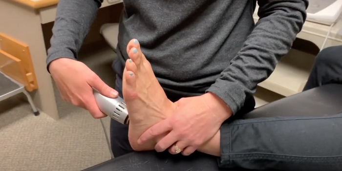 A female physical therapist manipulates the bottom of a female patients foot, using a handheld Radial Pulse Therapy tool to alleviate pain due to plantar fasciitis.