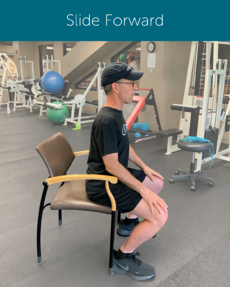 Orthopedic Institute physical therapist demonstrates how to stand from a sitting position beginning with sliding forward on your chair.